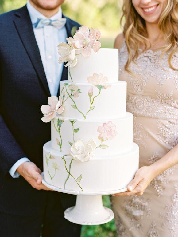 In questa foto due sposi tengono in mano una torta per matrimonio a più piani dipinta a mano, con fiori 3D