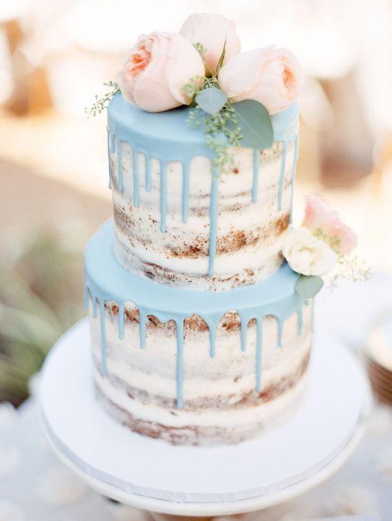 In questa foto una naked cake con effetto gocciolante e fiori come topper