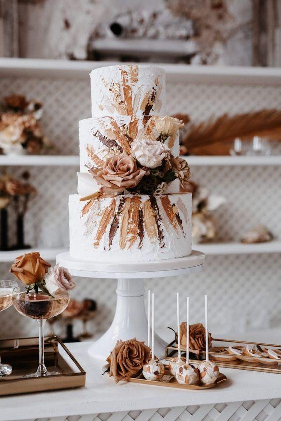 In questa foto una torta di matrimonio autunnale, decorata con un disegno nei toni del marrone chiaro e scuro