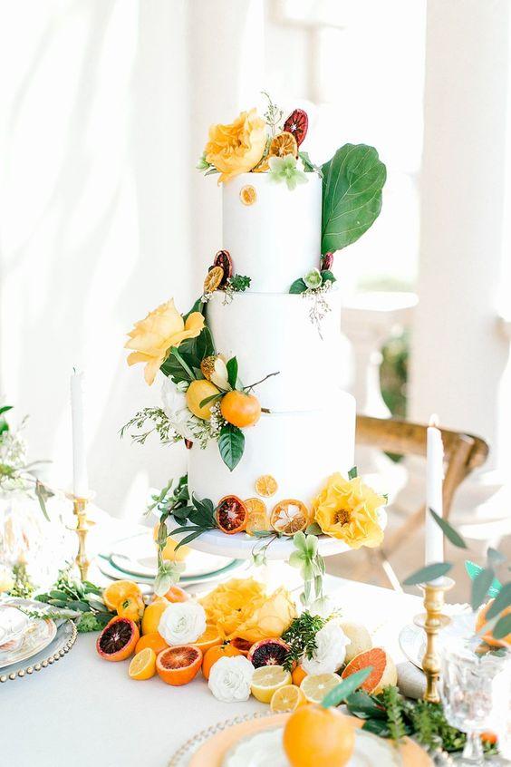 In questa foto una torta di matrimonio estiva decorata con agrumi e fiori nei toni del giallo e dell'arancio