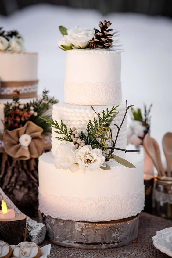 In questa foto una torta di matrimonio invernale: è tutta bianca, le decorazioni sono aghi di pino e pigne