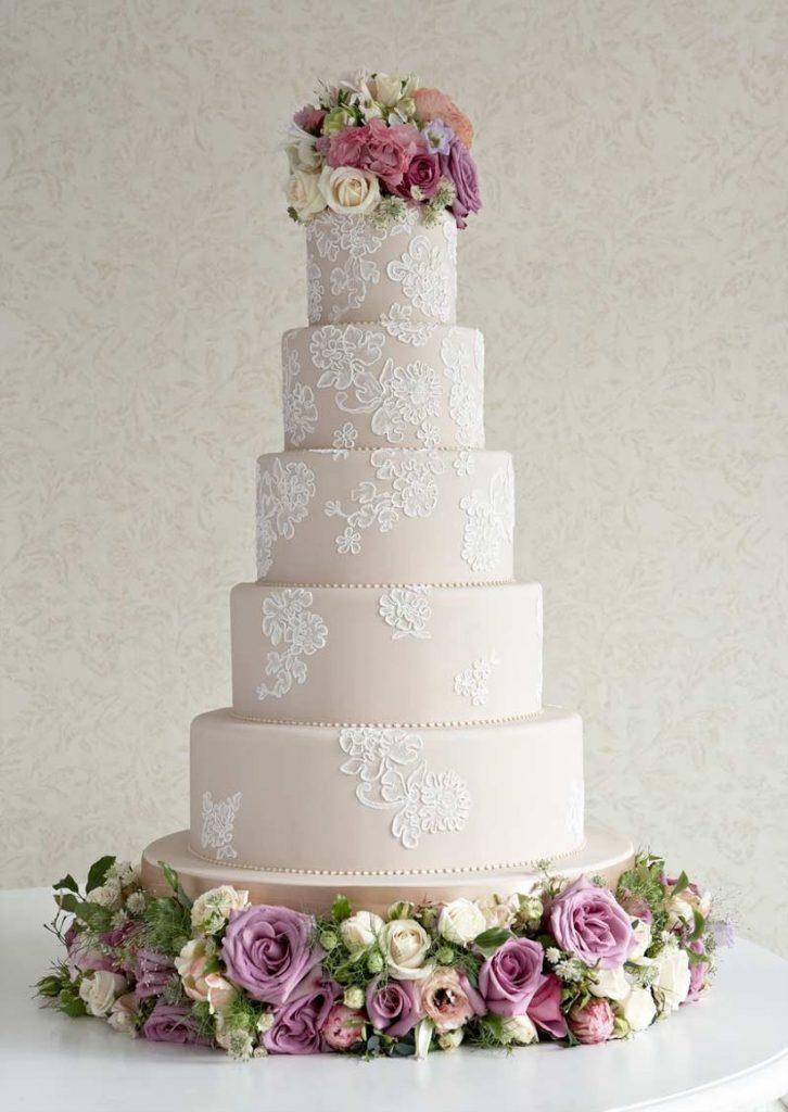 In questa foto una torta a 5 piani con una decorazione che ricorda la lavorazione del pizzo. Alla base e in cima fiori freschi