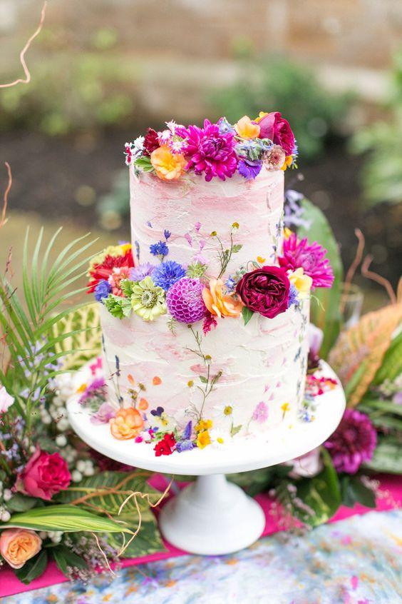 In questa foto una torta di matrimonio primaverile, decorata con fiori colorati edibili
