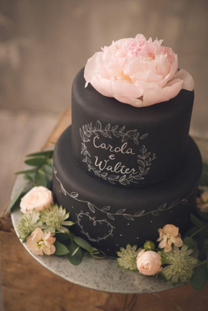 In questa foto la torta lavagna: sul piano più alto i nomi degli sposi e come topper una peonia rosa