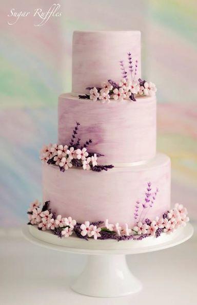 In questa foto una torta nei toni del lilla, decorata con fiorellini rosa
