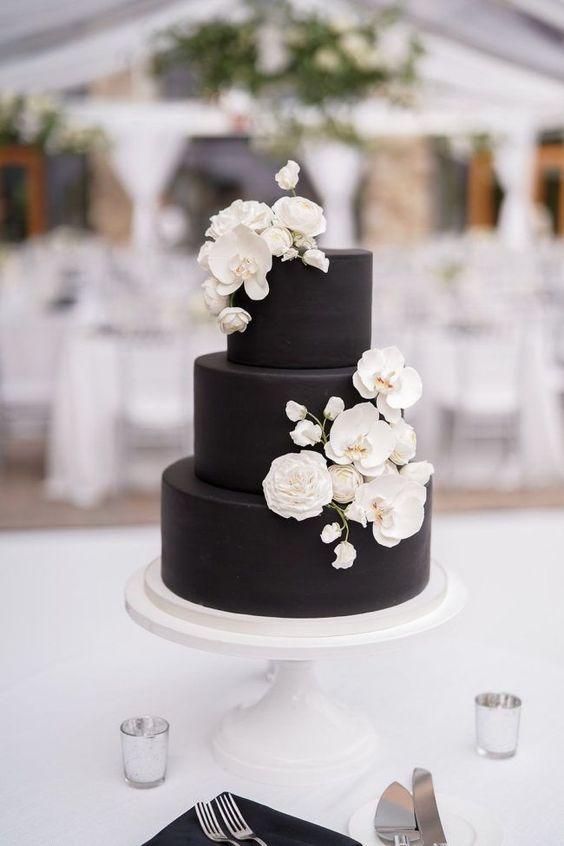 In questa foto una torta di matrimonio nera, decorata con rose e orchidee in pasta di zucchero bianche