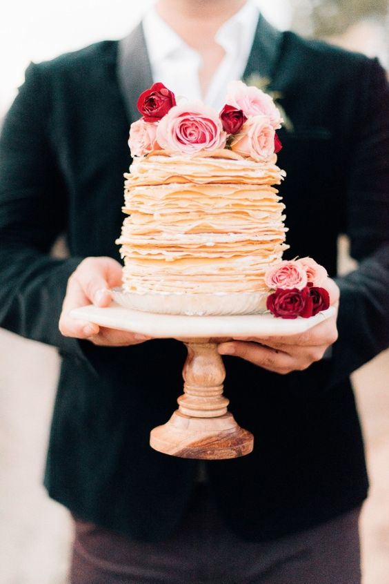 In questa foto uno sposo tiene in mano una Wedding Pancake decorata con rose come topper