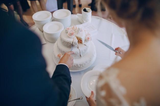In questa foto due sposi ripresi di spalle mentre tagliano la loro torta di matrimonio