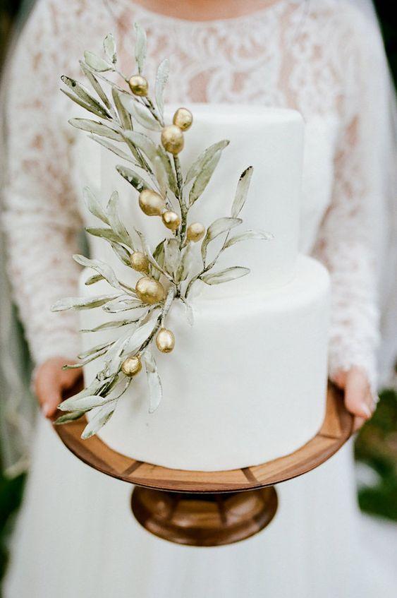 In questa foto una sposa tiene in mano una torta decorata con un ramoscello di ulivo