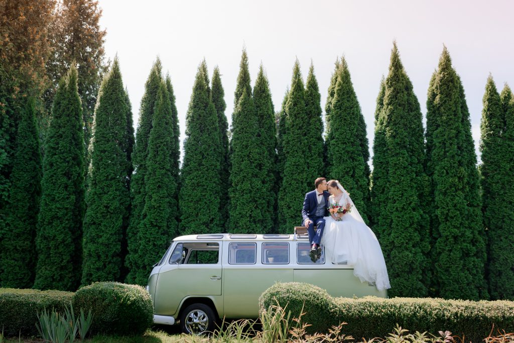 In questa foto una coppia di sposi seduta su un pullmino della WalksVagen scelto come auto da cerimonia per il loro matrimonio