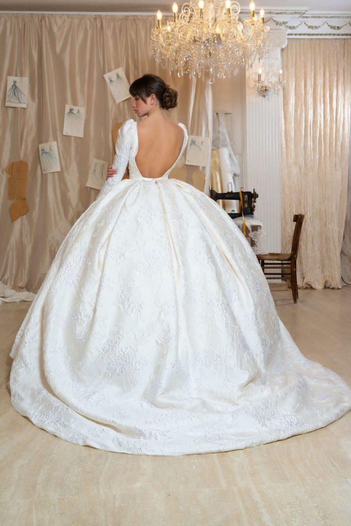 In questa foto una modella di spalle indossa un abito da sposa Amelia Casablanca 2022 presentato alla New York Bridal Fashion Week 2021