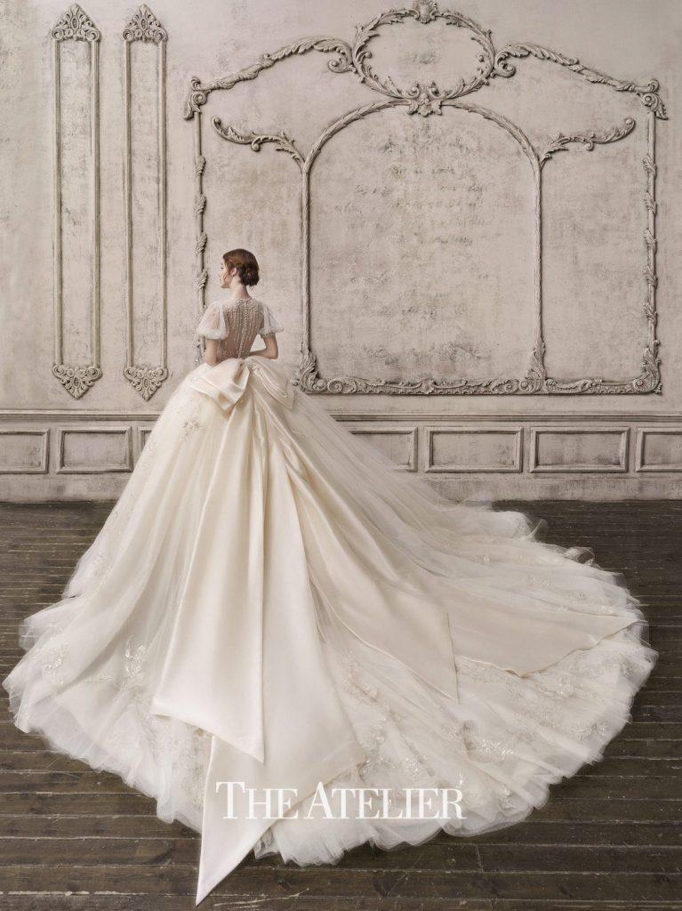 In questa foto una modella indossa un abito da sposa The Atelier Couture by Jimmy Choo 2022, presentato alla New York Bridal Fashion Week 2021