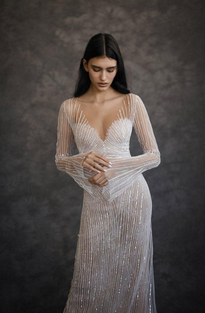 In questa foto una modella fotografata per tre quarti mentre indossa un abito da sposa Dana Harel 2022 presentato alla New York Bridal Fashion Week 2021