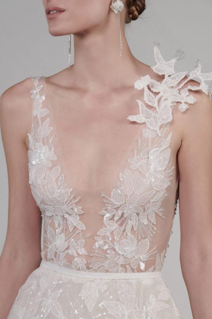 In questa foto il dettaglio del top di un abito da sposa Mira Zwillinger 2022: la scollatura è profonda e a V, sulla spalla un ramage floreale in pizzo 3D
