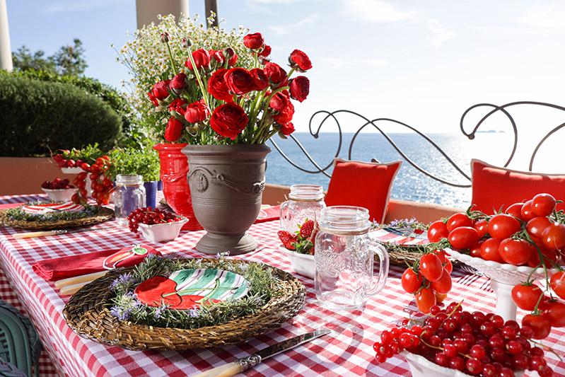 Un centro tavola con rose rosse e pomodorini rossi