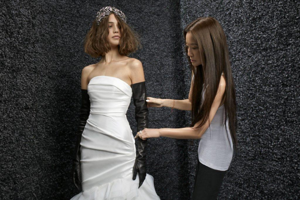 In questa foto la stilista Vera Wang sistema l'abito della modella che indossa uno dei suoi abiti da sposa per lo shooting fotografico della collezione con Pronovias