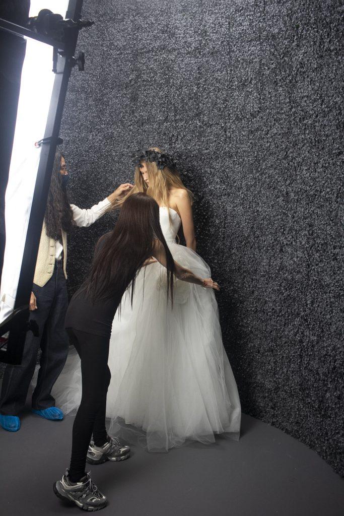 In questa foto la stilista sistema l'abito della modella che indossa uno dei suoi abiti da sposa per lo shooting fotografico della nuova collezione
