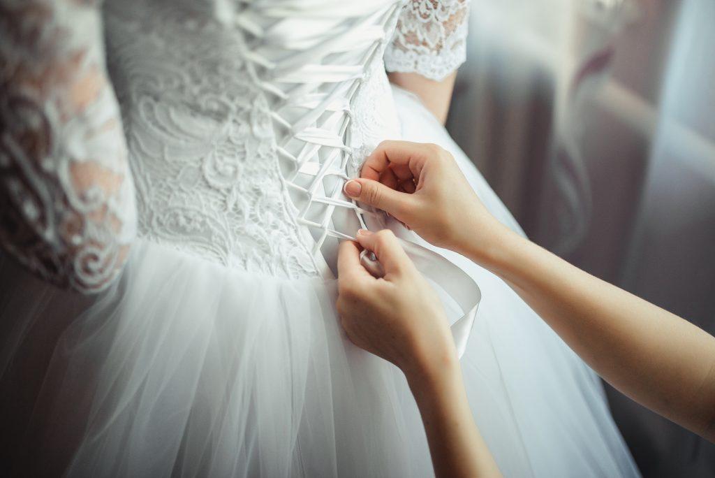 In questa foto il dettaglio posteriore del corpetto di un abito da sposa mentre una donna lo stringe in vita
