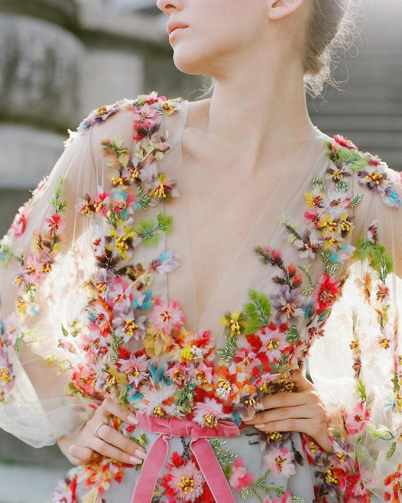 In questa foto il dettaglio del corpetto di un abito da sposa con ricami floreali 3D multicolor e fiocchetto in vita di velluto rosa