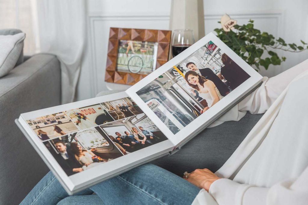 In questa foto una donna seduta sul divano in jeans e maglia bianca sfoglia il suo album di nozze aperto a metà