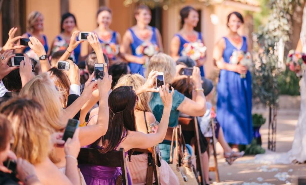 In questa foto gli invitati di un matrimonio scattano con i loro smartphone foto agli sposi durante la cerimonia di nozze. Sullo sfondo si intravedono fuori fuoco le damigelle d'onore vestite di blu con bouquet arancioni