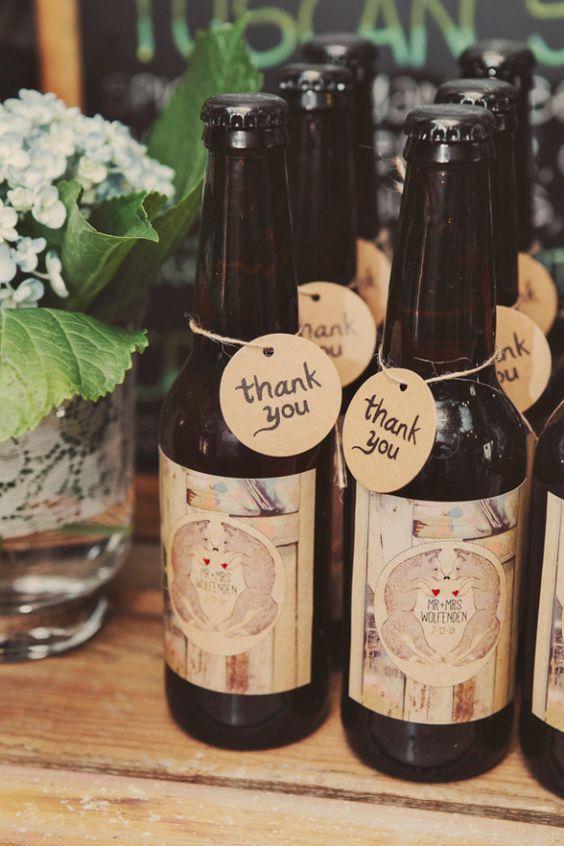 """In questa foto piccole bottiglie di birra usate come bomboniere. Al collo è legata una targhetta con su scritto """"Thank You"""" mentre le etichette sono personalizzate con il cognome degli sposi"""