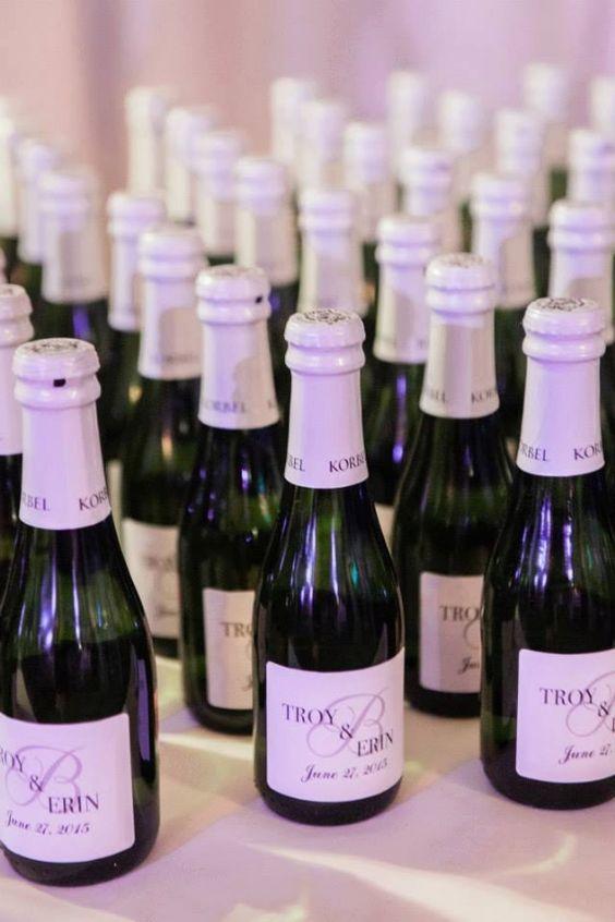 In questa foto piccole bottiglie di champagne con le etichette personalizzate con i nomi degli sposi e la data delle nozze, perfette per un matrimonio a tema vino