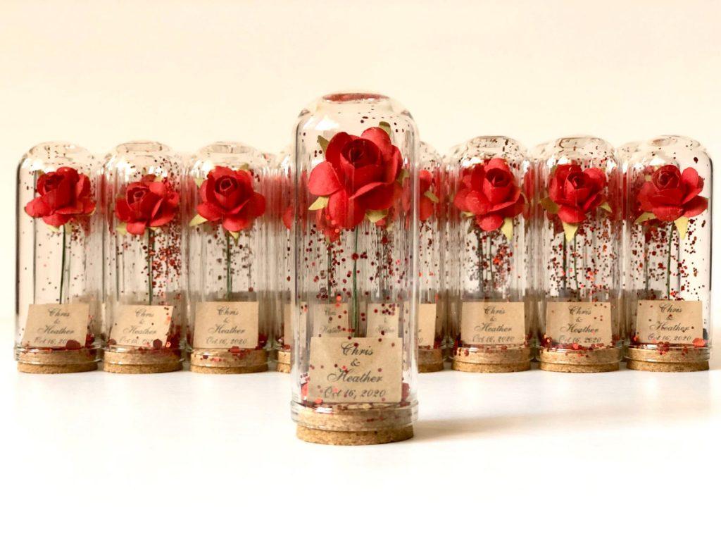 In questa foto piccole rose rosse di stoffa chiuse dentro campane di vetro decorate con brillantini in coordinato, perfette come bomboniere a tema Disney