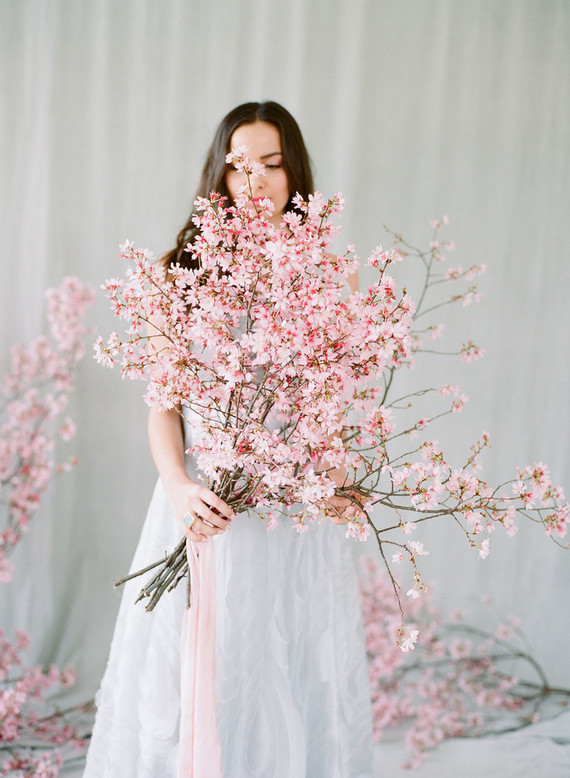 In questa foto un bouquet da sposa a braccio con rami di ciliegio