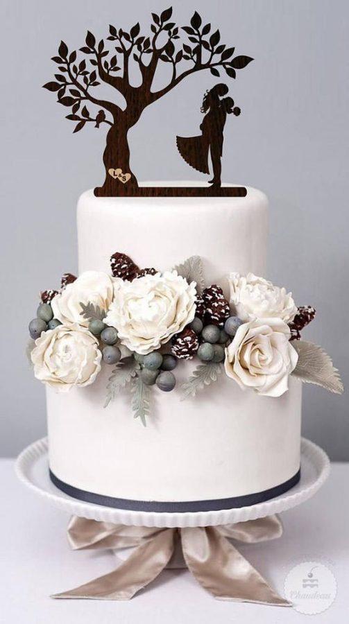 In questa foto un cake topper in legno a forma di albero della vita. Sotto la silhouette di due sposi che si abbracciano