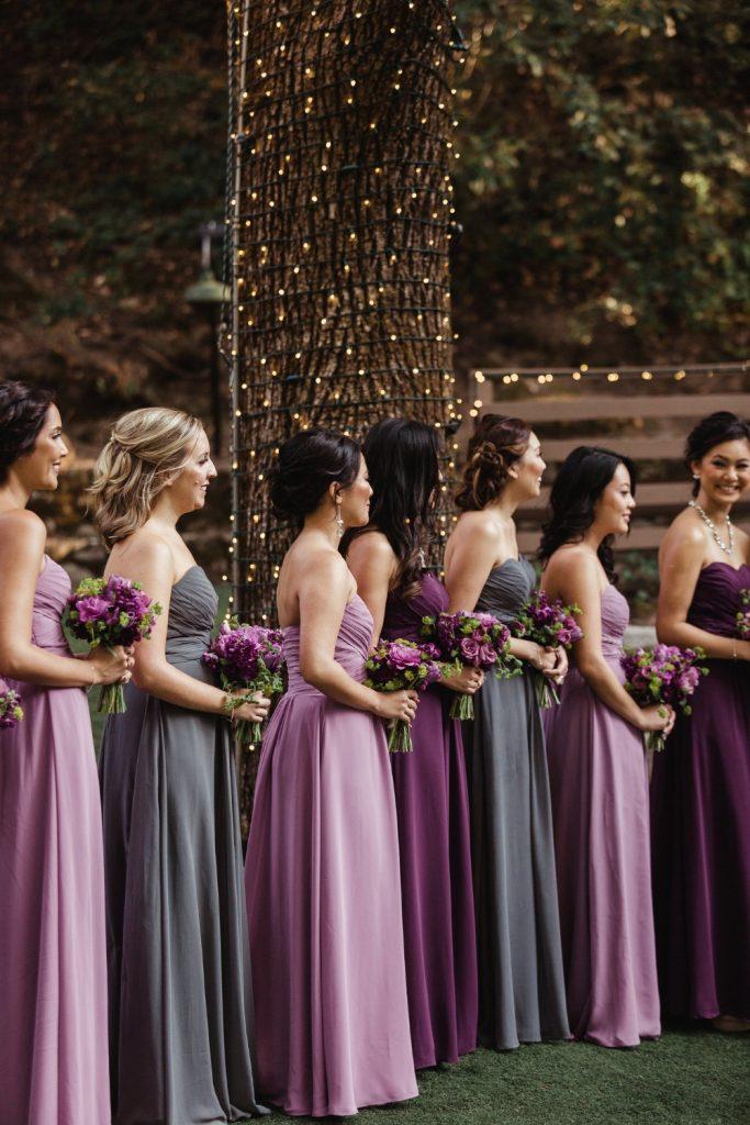 In questa foto sette damigelle guardano gli sposi durante la cerimonia all'aperto davanti ad un albero decorato con piccole luci. Indossano abiti a fascia nei colori malva, lilla e viola. Tengono tra le mani un piccolo bouquet viola e verde