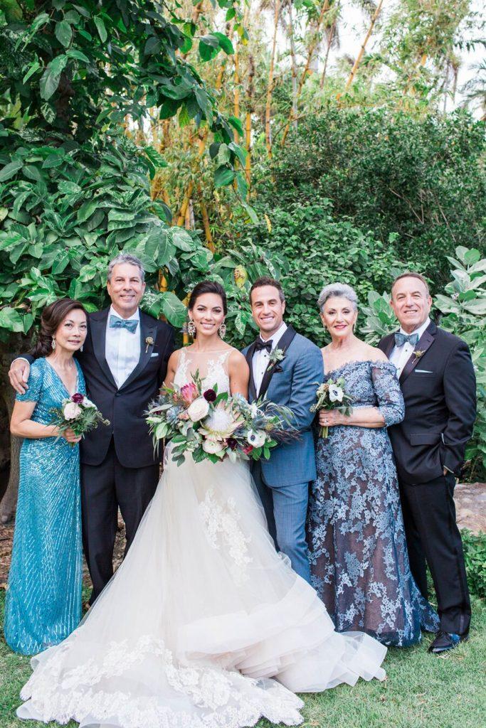 In questa foto due sposi posano in un giardino con i rispettivi genitori tutti con abiti e dettagli in blu. La sposa indossa un abito ampio e tiene tra le mani un bouquet a braccio di fiori colorati
