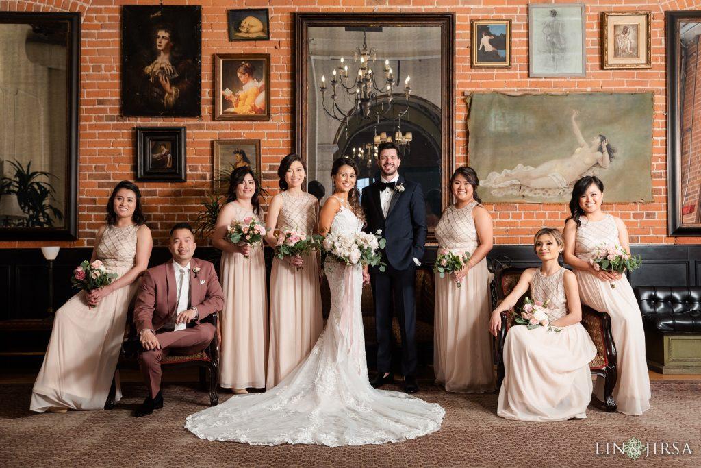In questa foto un Family Formal degli sposi con le damigelle e un testimone. Al centro i due sposi posano sorridenti e attorno a loro gli amici. La sposa indossa un abito a sirena con un lunga cosa, le damigelle abiti rosa pesca e tengono tutte tre le mani il bouquet