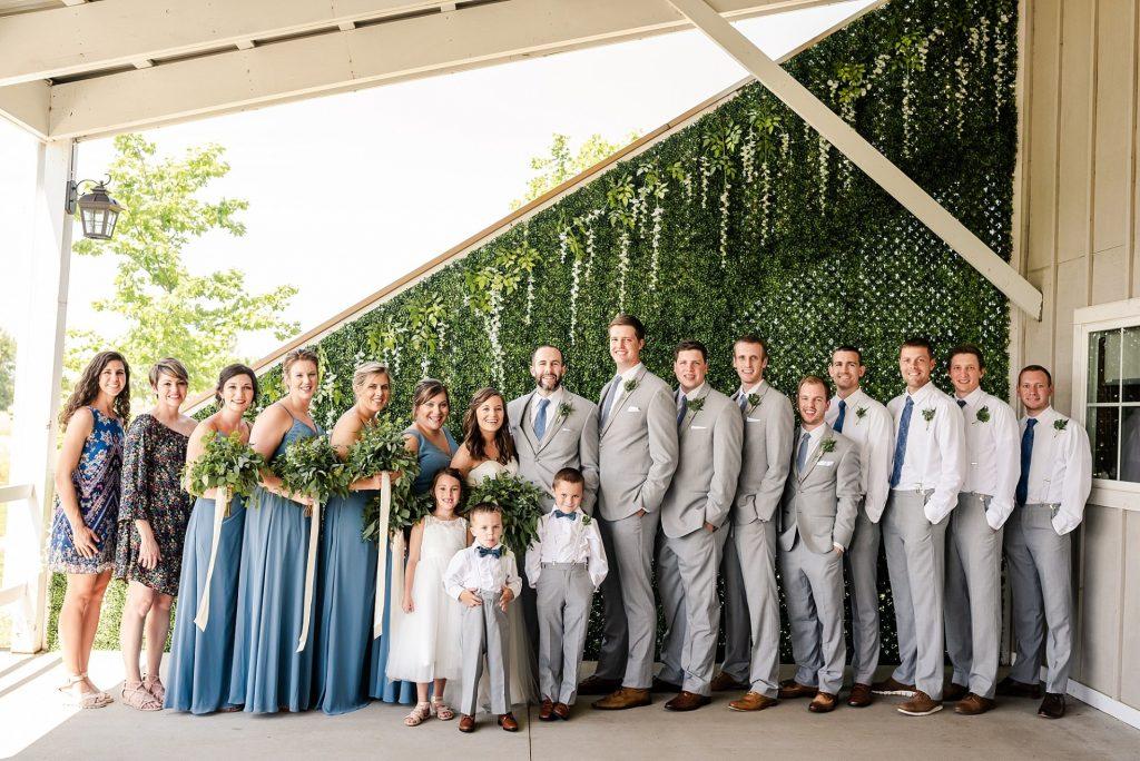 In questa foto due sposi posano con gli 8 testimoni in abito grigio perla come lo sposo, le 4 damigelle d'onore con abiti lunghi azzurro polvere e bouquet di foglie, due invitate, due paggetti e una damigella