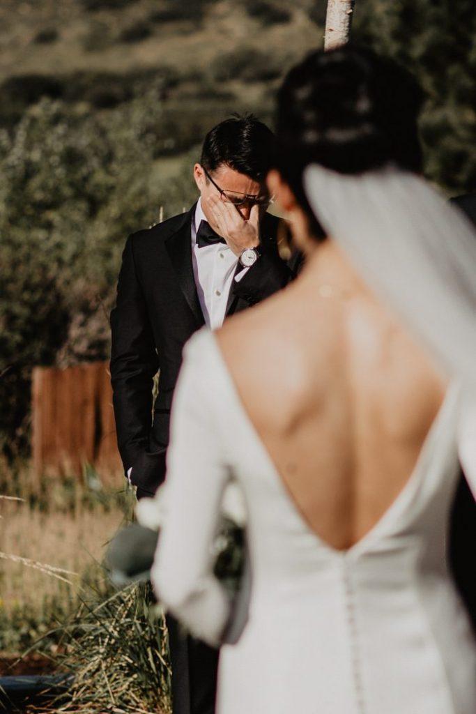 In questa foto lo sposo si commuove dopo aver visto la sua sposa, ritratta di spalle e fuori fuoco, per la prima volta in abito bianco