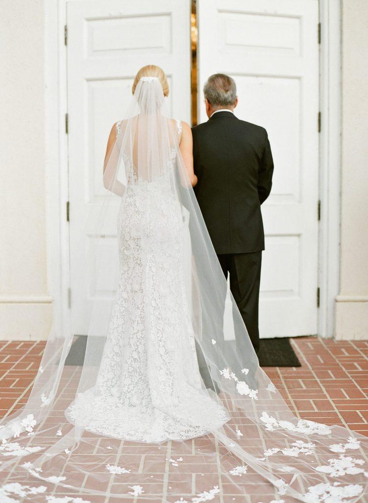 In questa foto la sposa e il papà ripresi di spalle prima di varcare la soglia della chiesa. La sposa tiene il braccio del papà