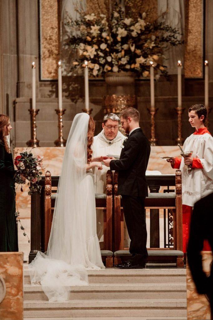 In questa foto due sposi all'altare si tengono per mano scambiandosi le promesse di nozze durante una cerimonia religiosa in chiesa