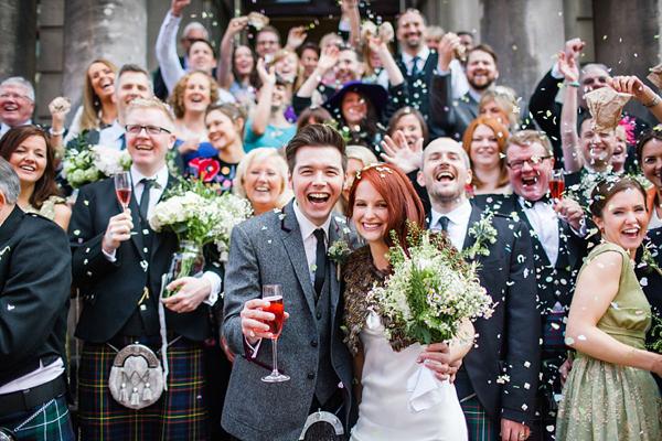 In questa foto due sposi sorridenti dopo la cerimonia di nozze scattano posano con gli ospiti che festeggiano dopo il Sì