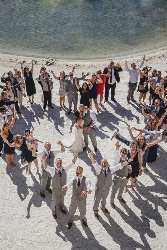 In questa foto realizzata con un drone gli invitati ad un matrimonio posano in riva ad un lago formando un cuore. Al centro gli sposi si baciano abbracciati