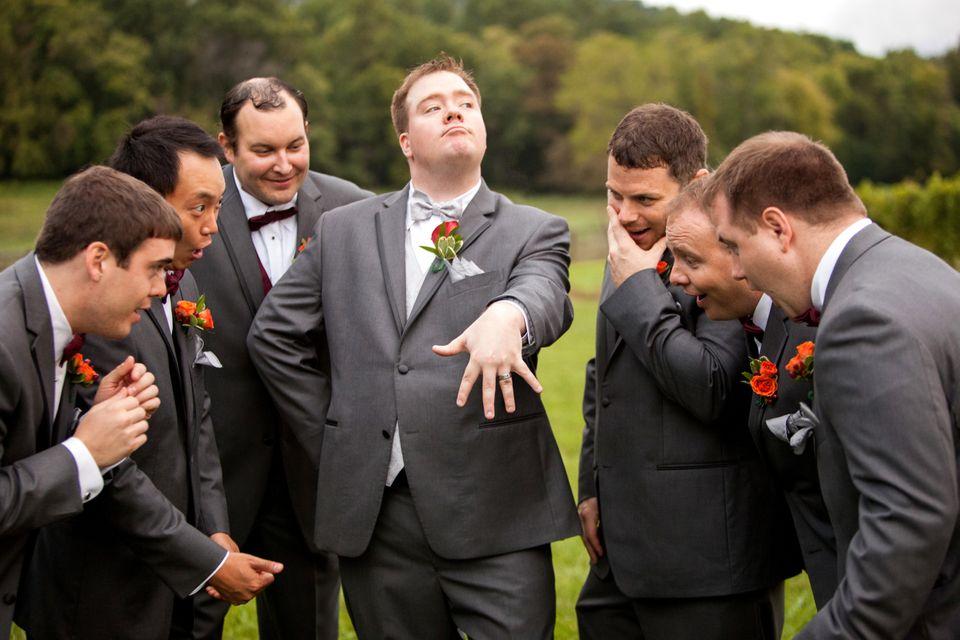 In questa foto lo sposo scherza con i testimoni mostrando con orgoglio la fede nuziale