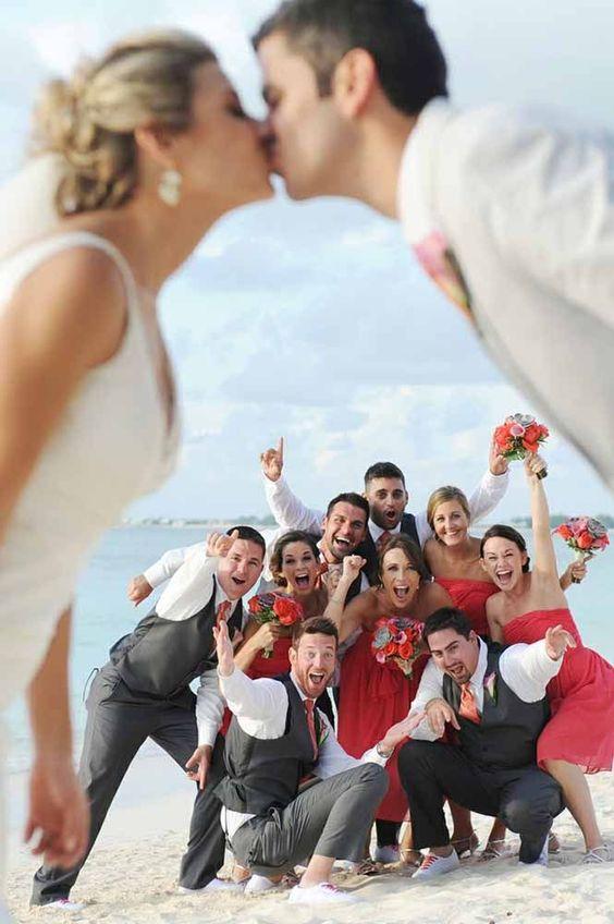 In questa foto gli sposi in primo piano fuori fuoco si baciano facendo da cornice a testimoni e damigelle vestite di rosso che posano in gruppo sullo sfondo in spiaggia in riva al mare