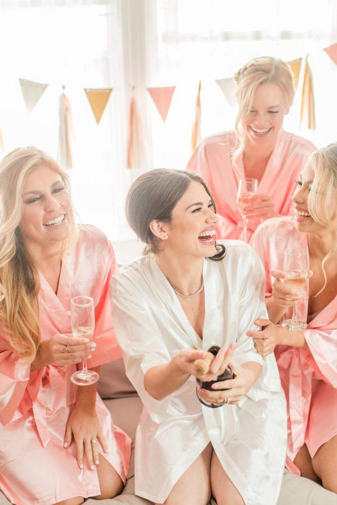 In questa foto la sposa scherza e brinda ridendo con le sue damigelle durante la preparazione