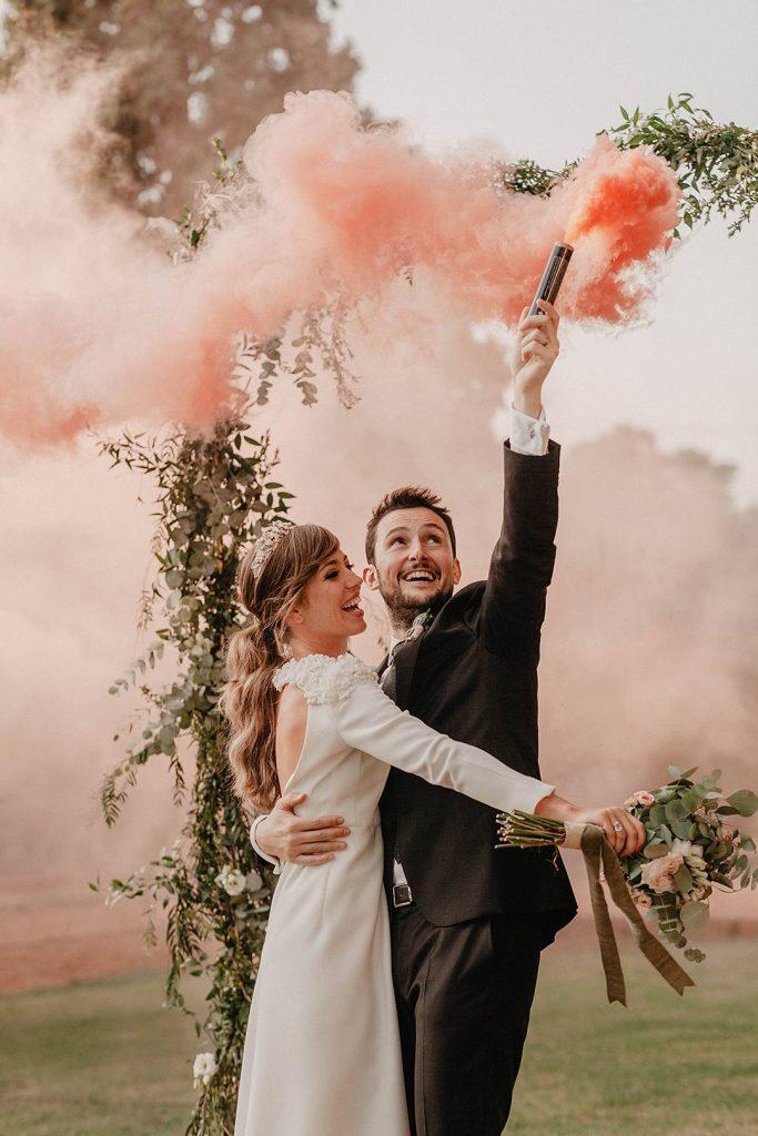 In questa foto due sposi sorridenti si abbracciano su un prato mentre lo sposo agita un bengala di fumo rosso