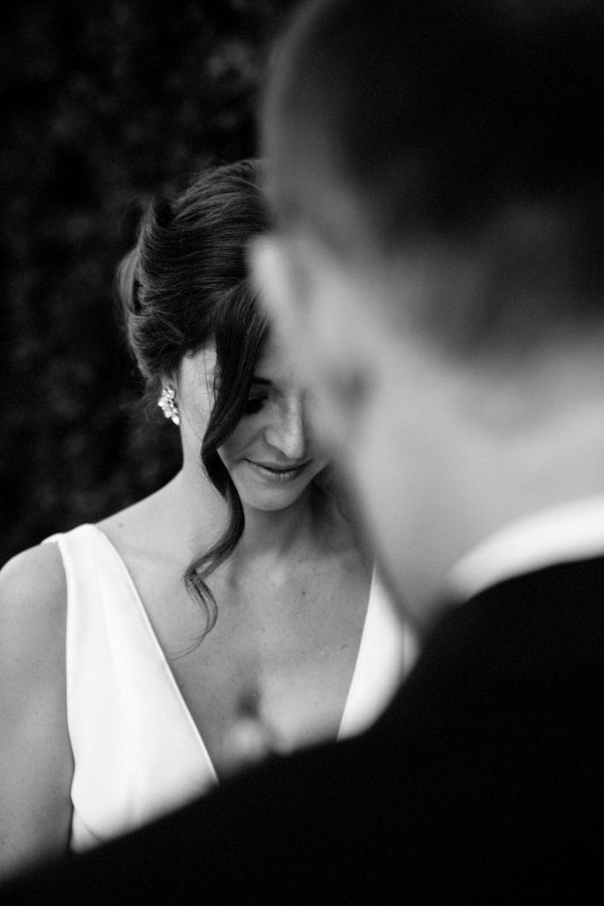 In questa foto in bianco e nero la sposa ripresa davanti lo sposo che si intravede sfocato pronuncia le promesse di matrimonio all'altare