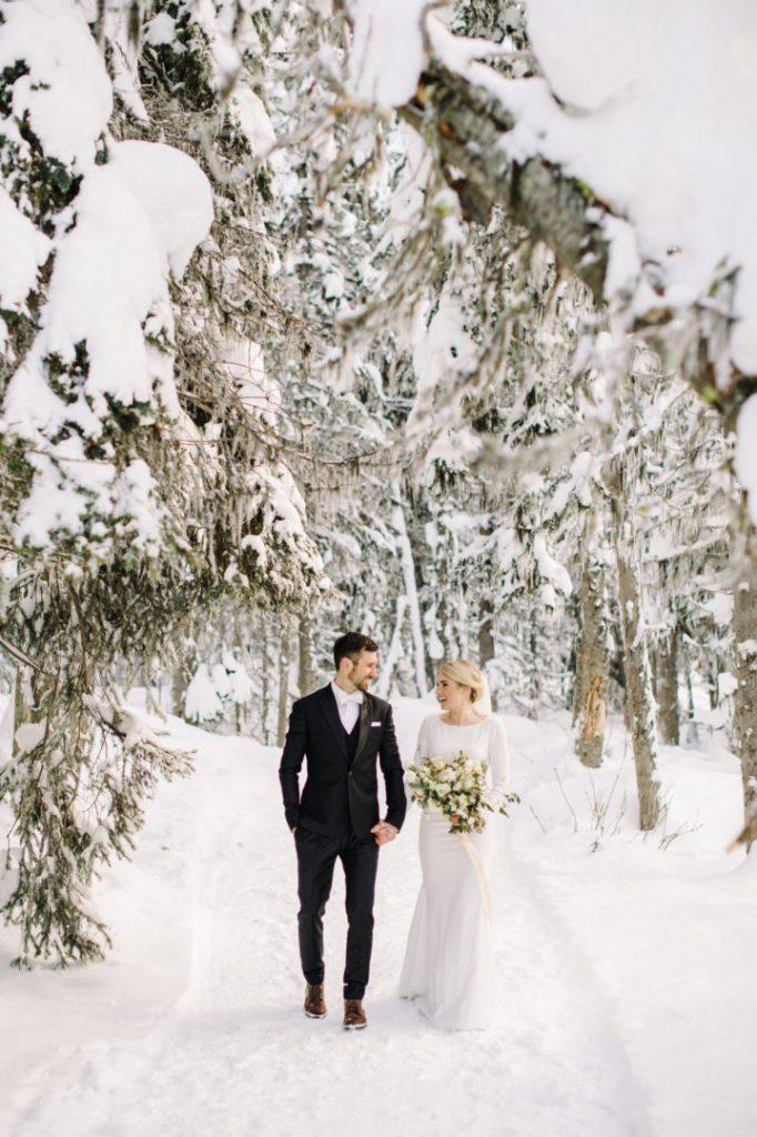 In questa foto due sposi camminano lungo il sentiero di un bosco di montagna innevato. Si guardano sorridendo e la sposa tiene tra le mani il suo bouquet di fiori bianchi