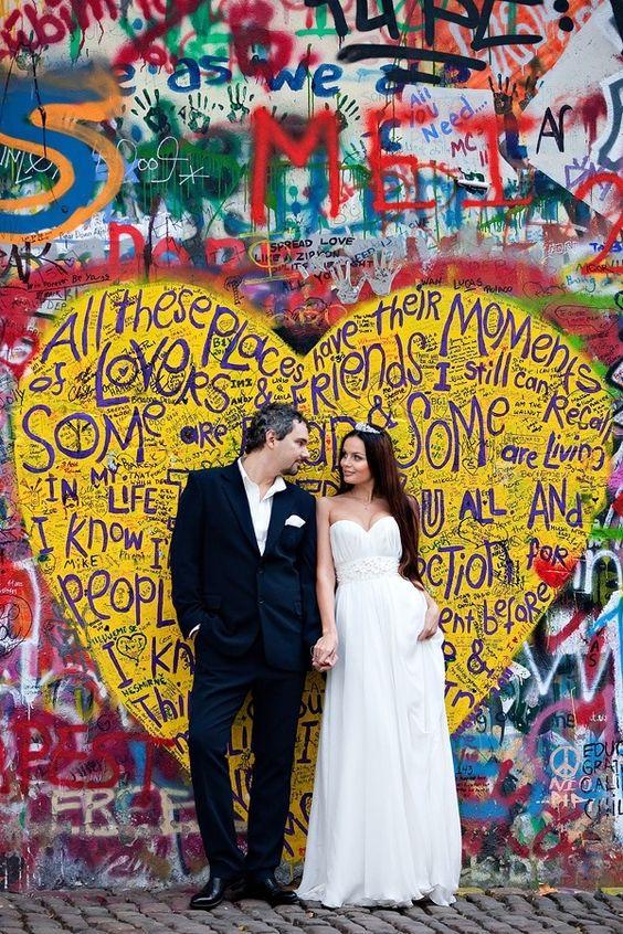 In questa foto due sposi si guardano e posano davanti ad un murales a forma di cuore giallo con scritte ispirate all'amore