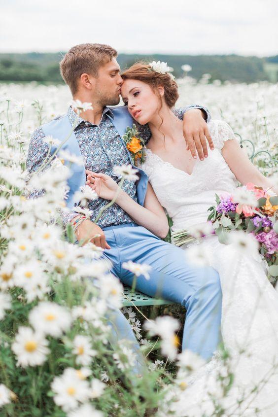 In questa foto due sposi posano dopo la cerimonia immersi in un prato di margherite. La sposa ha la testa appoggiata sulla spalla dello sposo, vestito d'azzurro, che la bacia sulla fronte
