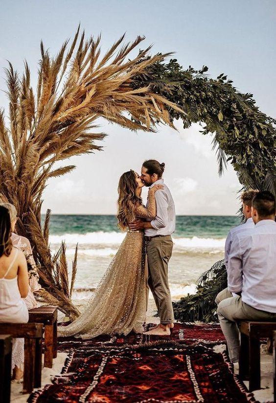 In questa foto due sposi si baciano alla fine della cerimonia di matrimonio sulla spiaggia in riva al mare davanti ad un arco di pampas e foglie mentre tutti gli ospiti li guardano