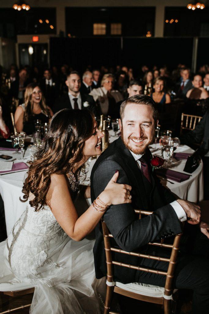 In questa foto due sposi ridono seduti al tavolo con alcuni ospiti durante il ricevimento