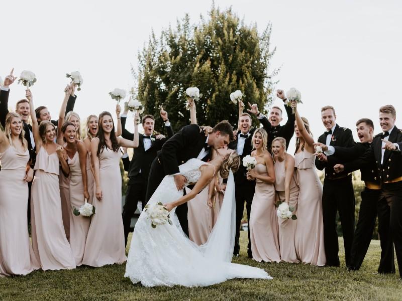 In questa foto una coppia di sposi posa con damigelle e testimoni. Lo sposo fa fare un casqué alla sposa mentre la bacia. Damigelle e testimoni festeggiano e alzano in aria i bouquet